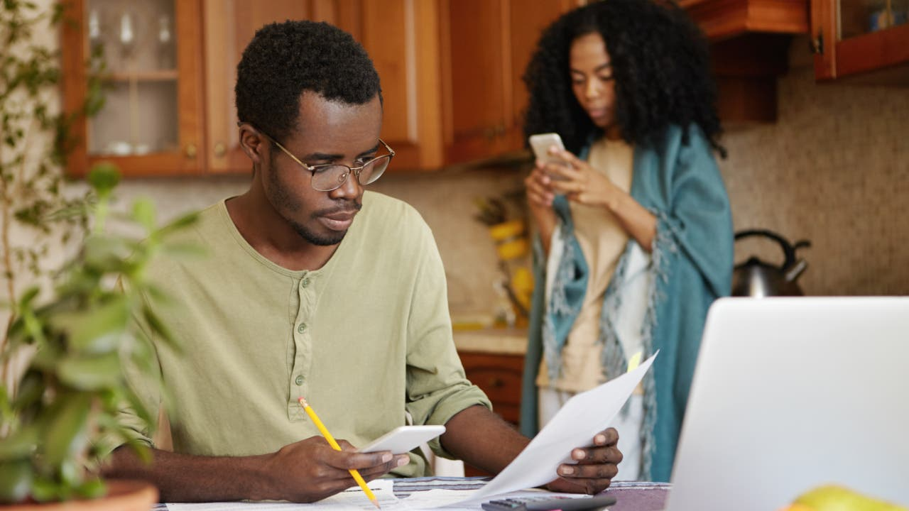 Man sits at kitchen table with pen and paper while woman stand behind on cell phone
