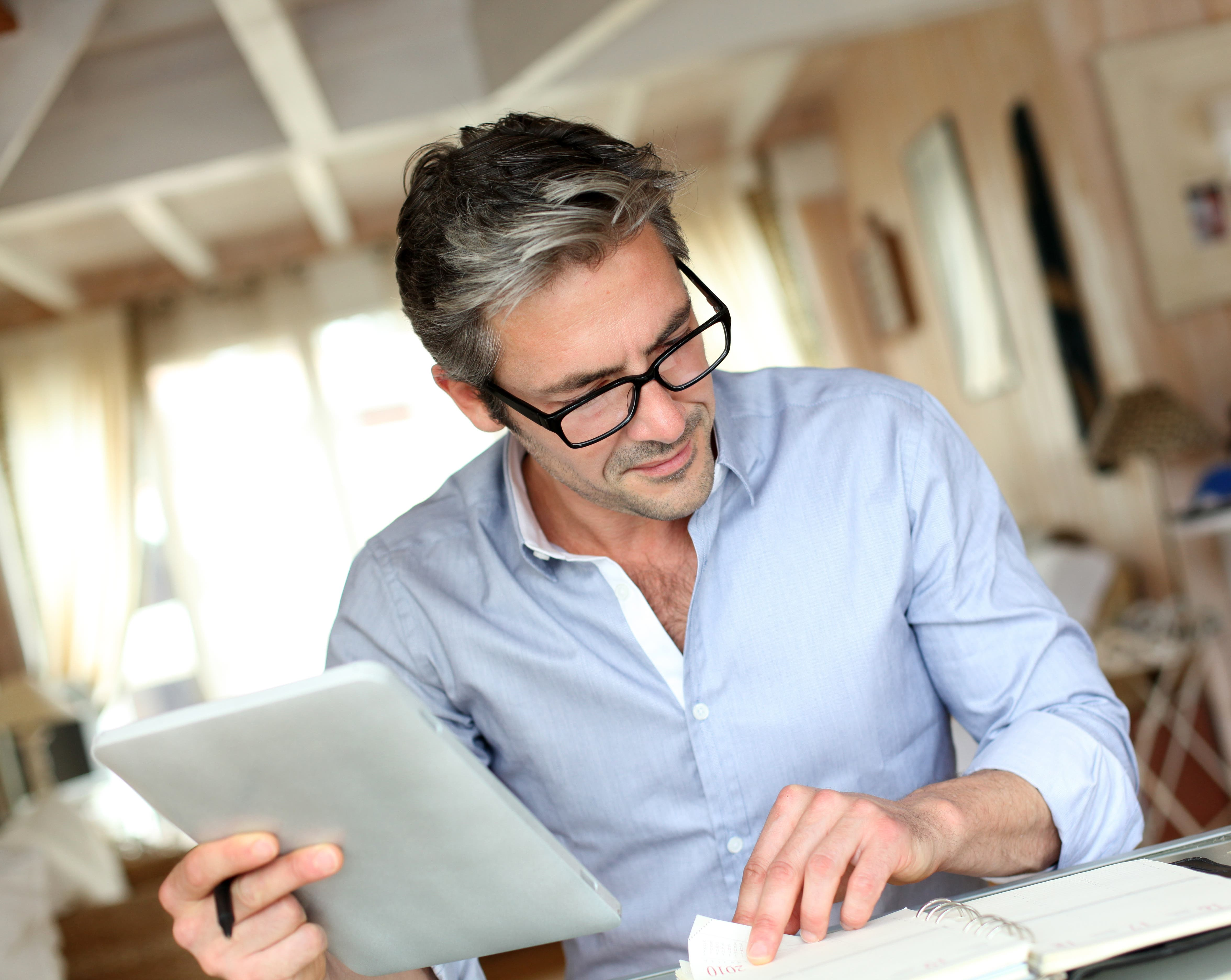 Older businessman working with paperwork and tablet