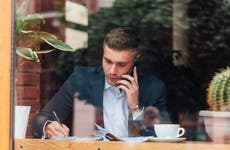 man on cell phone viewed through cafe window