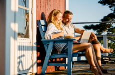 Couple having breakfast on their porch at their cabin