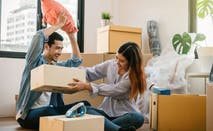 Young Asian couple unpack moving boxes in new apartment