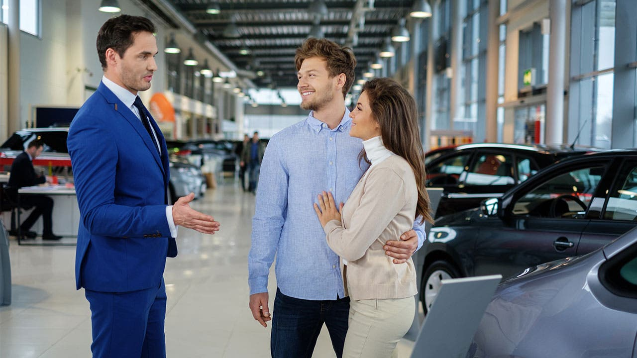 Couple talking with car dealer