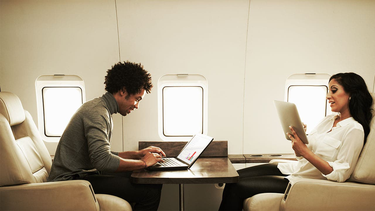 People working on laptops on a private jet