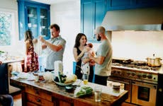 husband and wife with new baby in kitchen