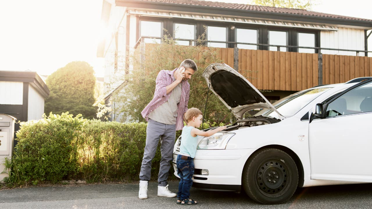 father and son working on car in front of house