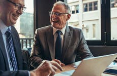 Two older successful businessman laugh during cafe business meeting