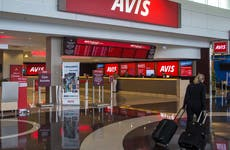 Woman walking towards Avis rental cars in airport