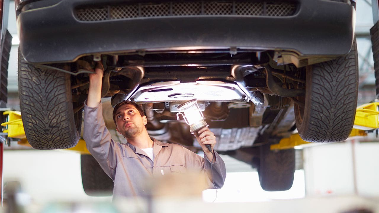 Auto mechanic inspecting a car