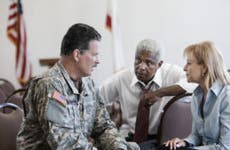 A military veteran discusses financing and insurance options with some experts.