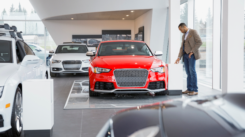 man looking at new car at dealership