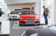 man looking at new car at dealership