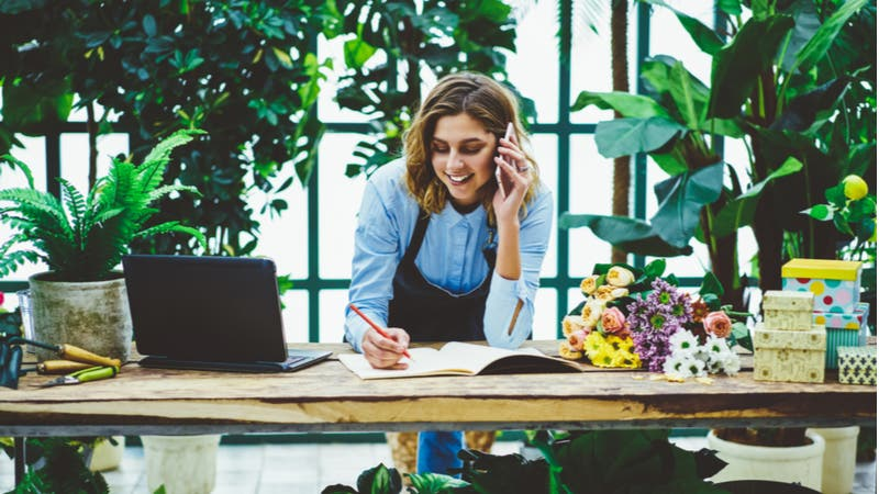 Florist works on paperwork while on the phone