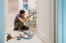man working on plumbing in home