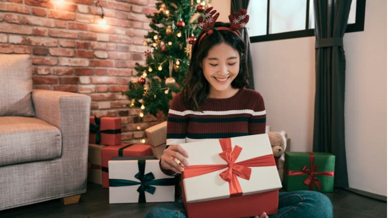 Young Asian woman opens Christmas gift box