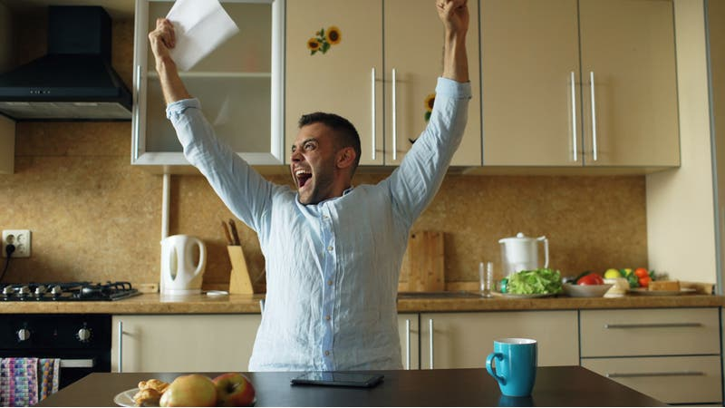 Man opens letter with good news and celebrates