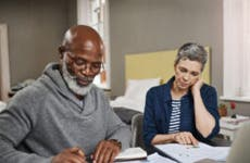Older interracial couple sitting together at a desk and reviewing their options financially.