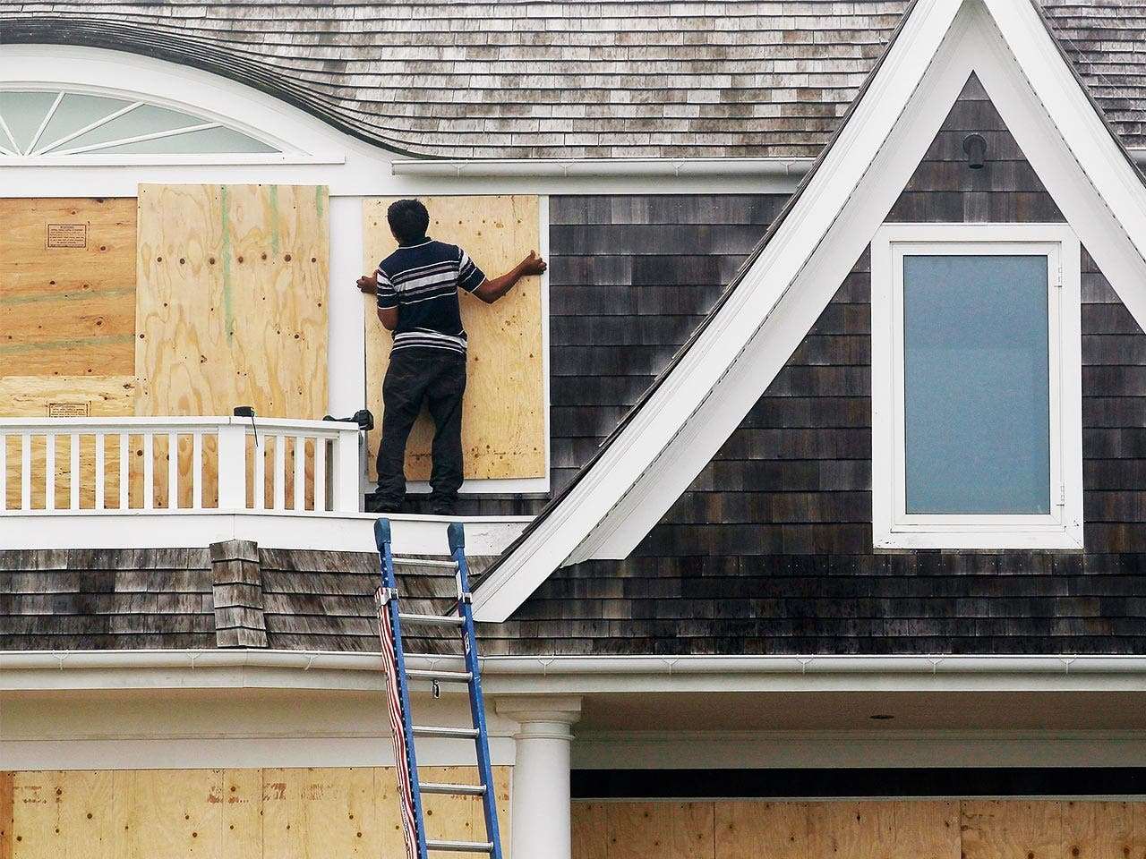 Man installing plywood over windows to avoid damage