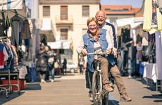 Older couple ride a bicycle together through a market
