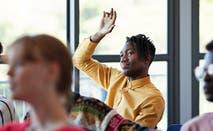 Student raises his hand in college classroom