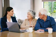An older couple sits with a young woman who is a financial specialist. She is reviewing their options.
