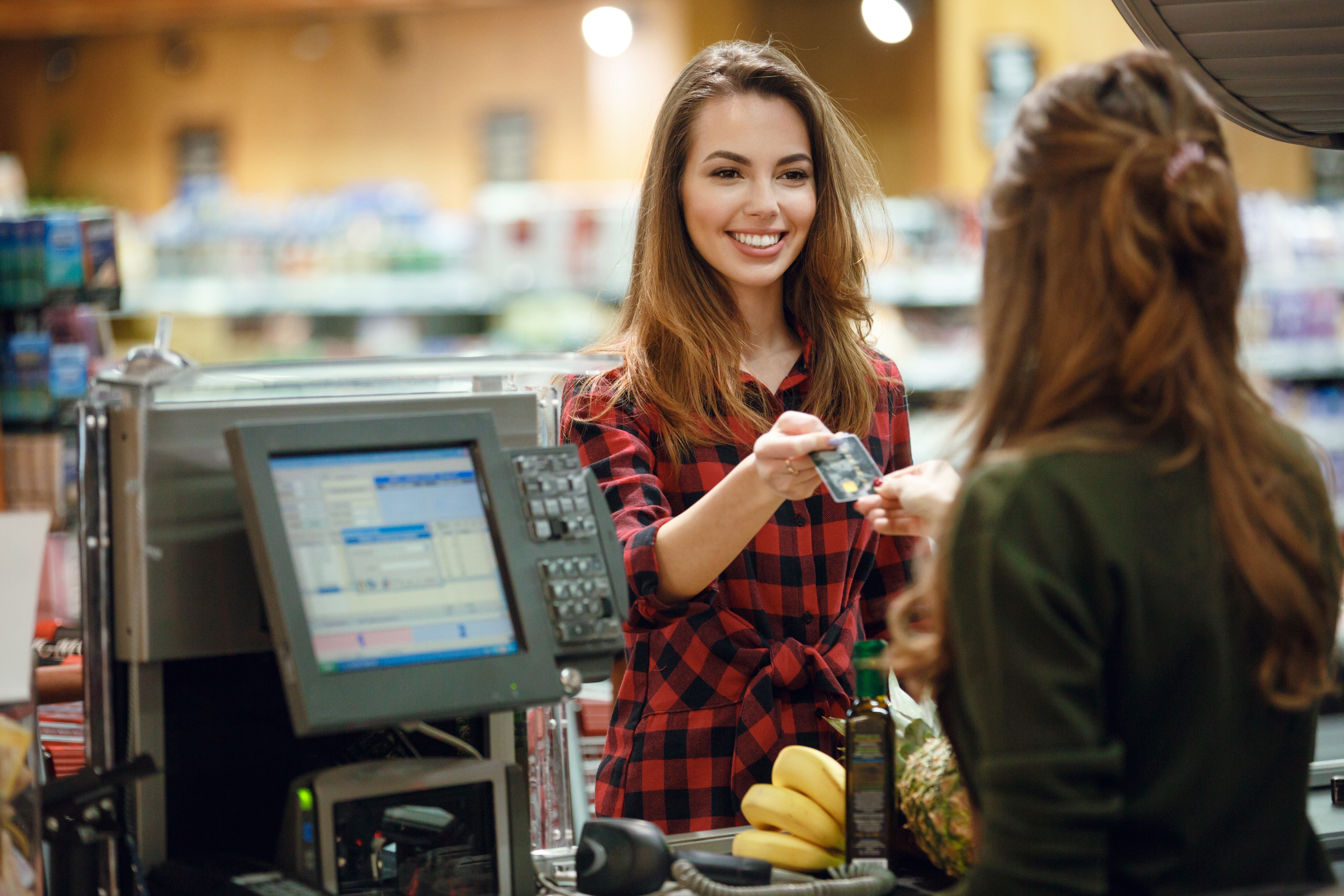 young woman pays for groceries with credit card