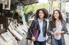 Two female friends browse books at an outdoor stand