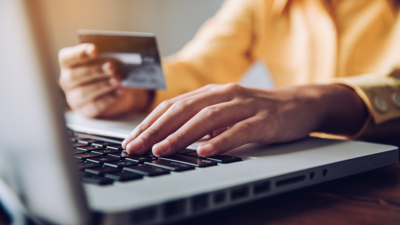 Cropped Hand Of Businessman Holding Credit Card While Using Laptop In Office