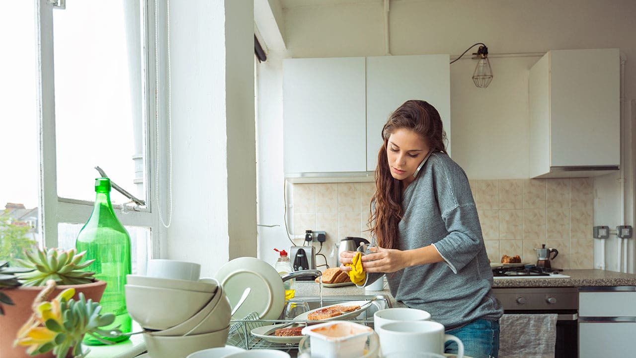 Woman on phone doing dishes
