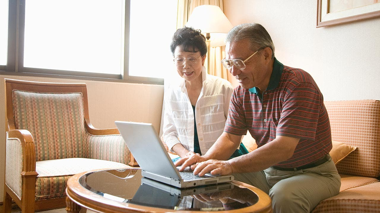 Senior couple using laptop in their living room