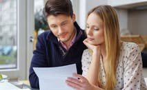 Two people look over financial documents together