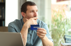 Man looks out window while holding a credit card