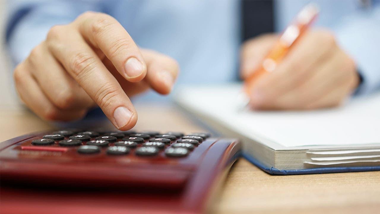 Man looking at notepad calculating budget