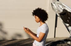Woman looks at phone during car breakdown.