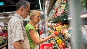 Older couple shopping in the produce section of grocery store