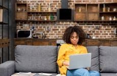 Young woman works on laptop from home