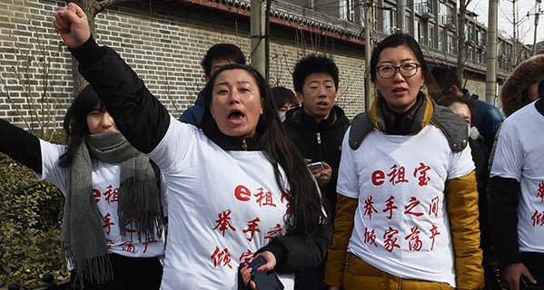 Investors in Chinese online peer-to-peer lender Ezubao chant slogans during a protest in Beijing on February 4, 2016. The protest came days after China announced that 21 people had been arrested on suspicion of defrauding around 900,000 people of more than 50 billion yuan (7.6 billion USD), after Ezubao turned out to be a giant Ponzi scheme. The T-shirts read 'Ezubao: Raise hands, lose a family fortune', a play on the company's slogan. AFP PHOTO / GREG BAKER / AFP / GREG BAKER