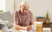 Elderly man works on finances