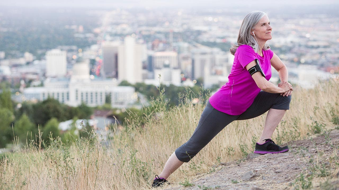 Woman stretching on a hill outside the city