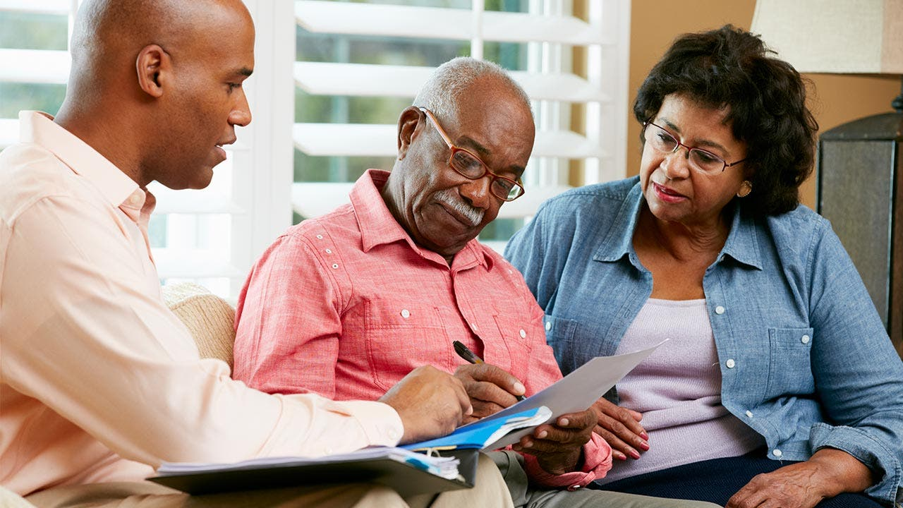 Older couple sitting with financial adviser