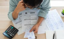 Person looking at a stack of credit card bills