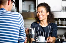 Smiling barista holding coffee cup and a customer © iStock