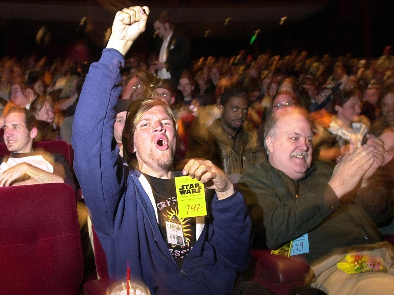 Fan cheering at movie premiere while holding up his numbered ticket