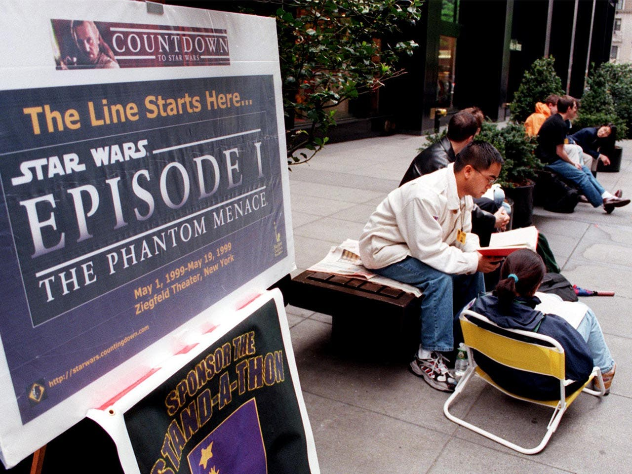 "People sitting on a bench next to a ""Star Wars: Episode I — The Phantom Menace"" poster"