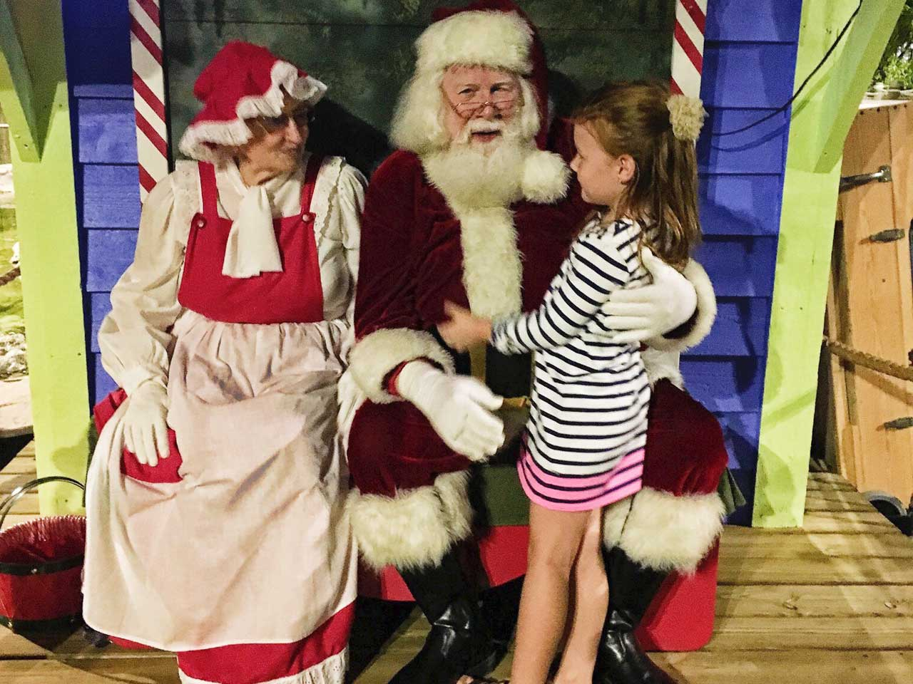 Little girl talking to Santa and Mrs. Claus | Katie Doyle/Bankrate