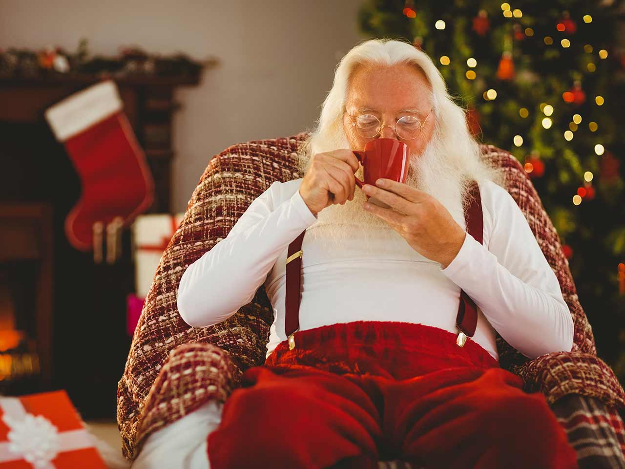 Santa sitting on chair, drinking hot cocoa | Wavebreakmedia/iStock/Getty Images Plus/Getty Images