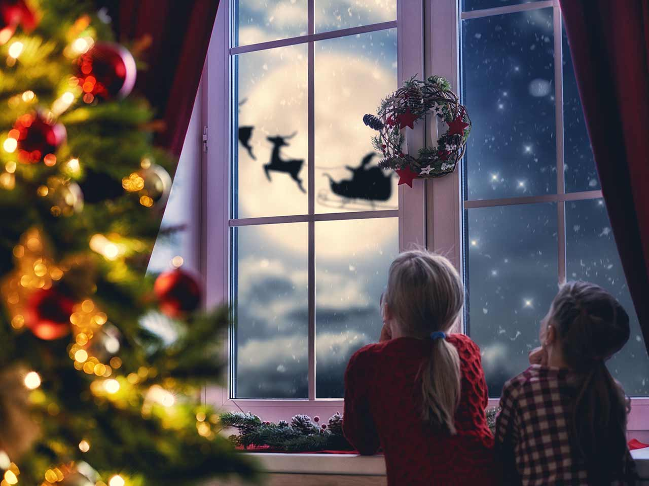 Children watching Santa in sleigh | Choreograph/iStock/Getty Images Plus/Getty Images