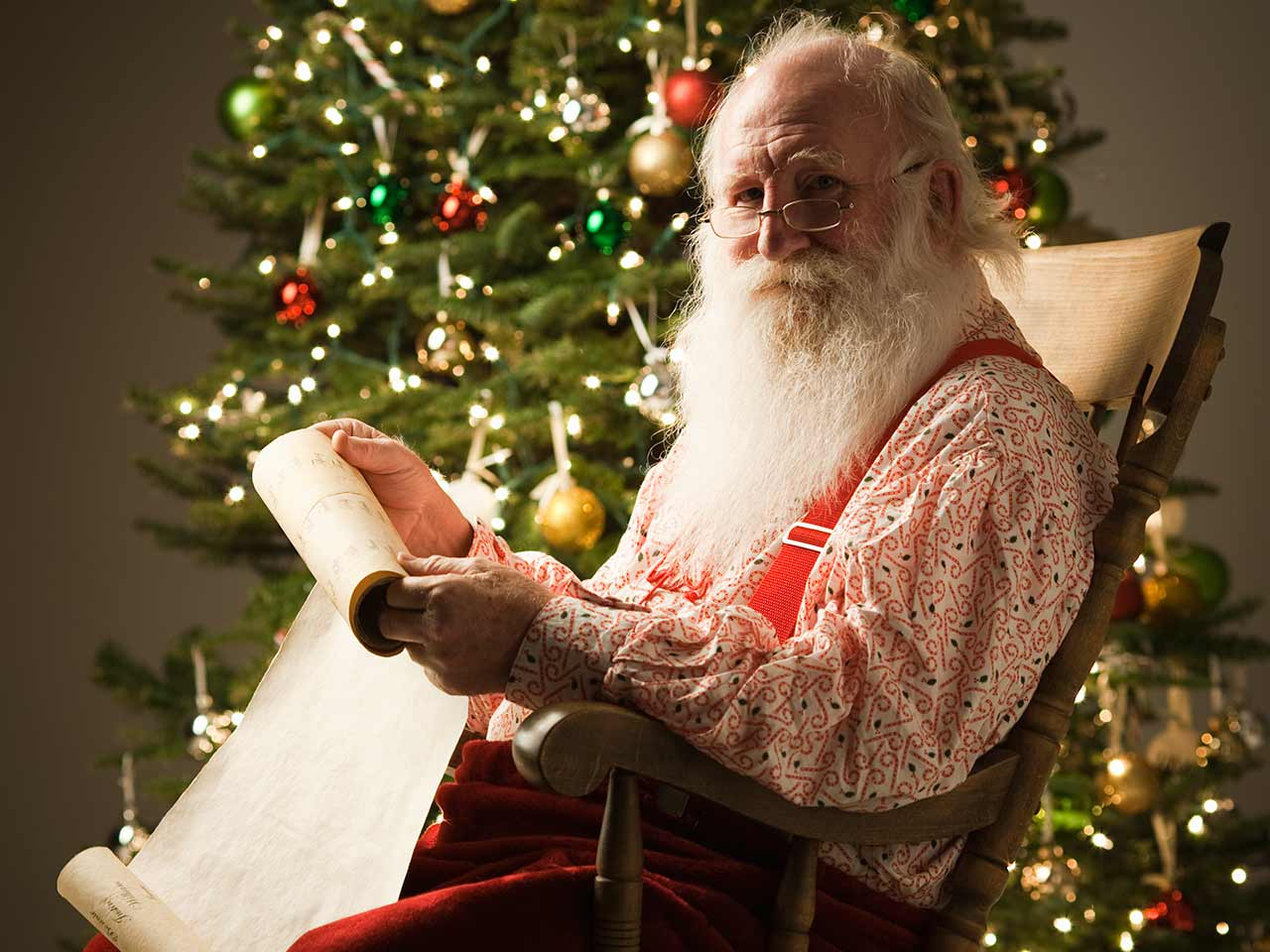 Santa Claus checking his list | RubberBall Productions/Getty Images