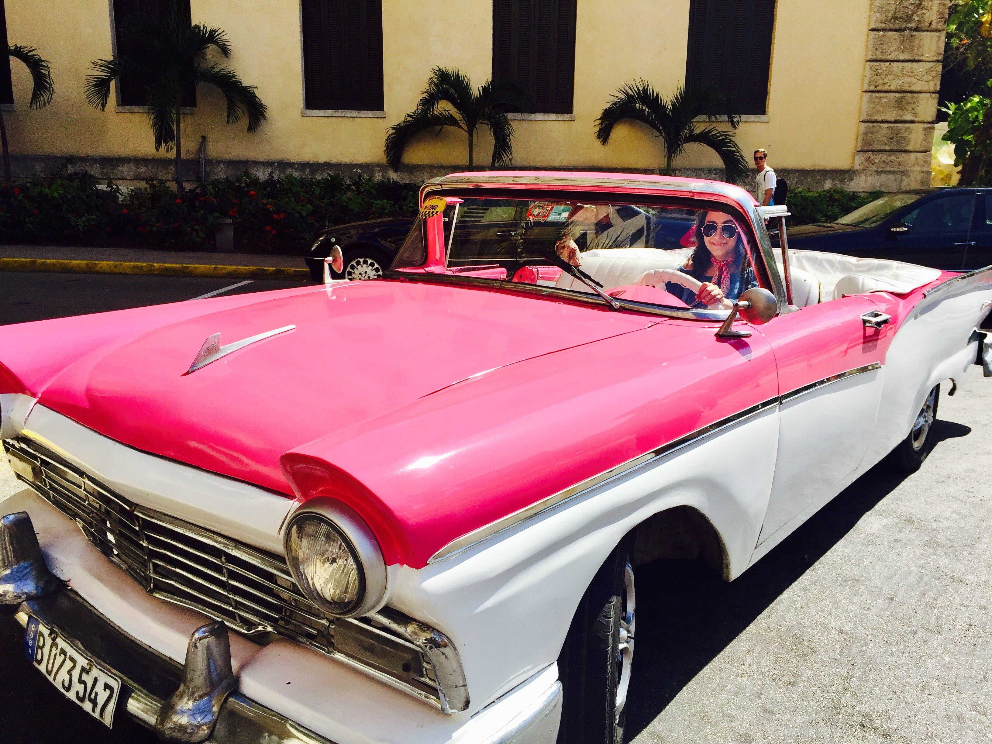 Retro cars zoom down the streets in Havana.