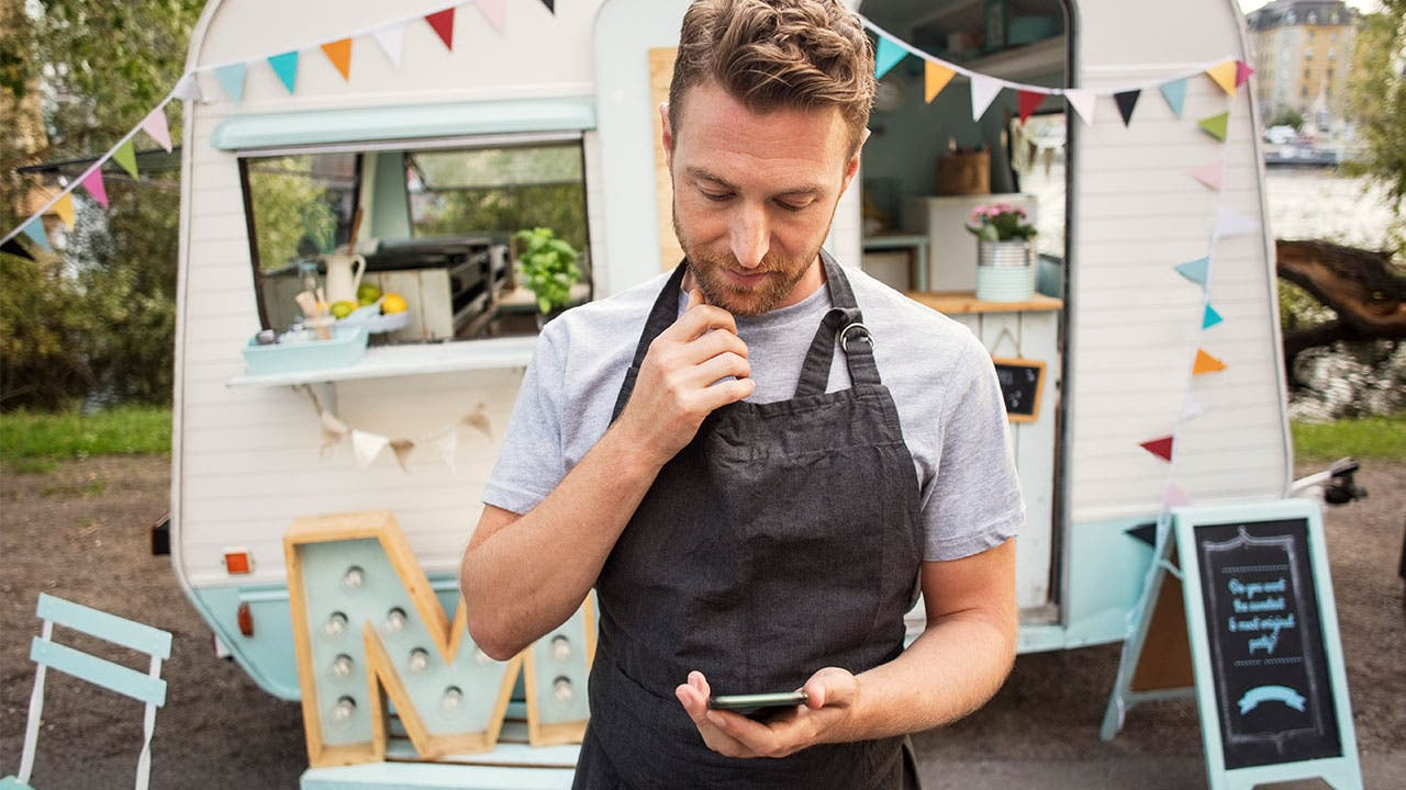 Man wearing apron and looking at phone