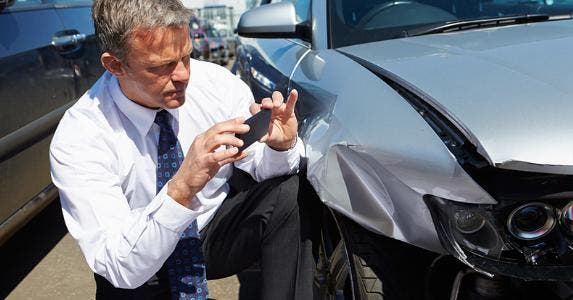 Man taking picture of totaled car © Monkey Business Images/Shutterstock.com